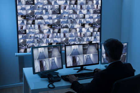 Photo pour Rear View Of A Man In Control Room Monitoring Multiple Cctv Footage - image libre de droit