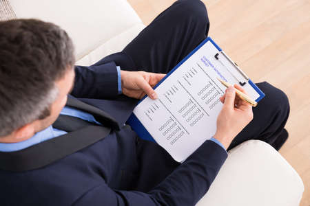 Photo pour High Angle View Of Businessman Sitting On Couch Filling Customer Survey Form - image libre de droit