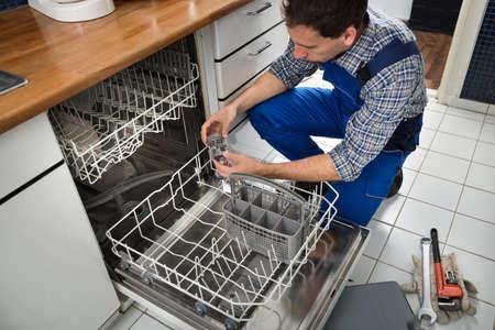 Photo pour Portrait Of Male Technician Repairing Dishwasher In Kitchen - image libre de droit