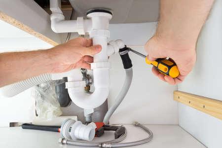 Foto de Close-up Of A Male Plumber Repairing Sink In Bathroom - Imagen libre de derechos