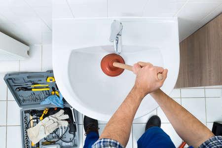 Foto de High Angle View Of Male Plumber Using Plunger In Bathroom Sink - Imagen libre de derechos