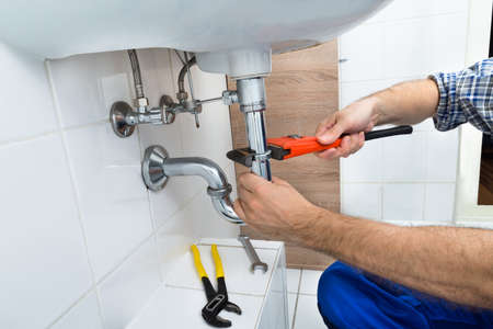 Foto de Close-up Of Male Plumber Fixing Sink In Bathroom - Imagen libre de derechos