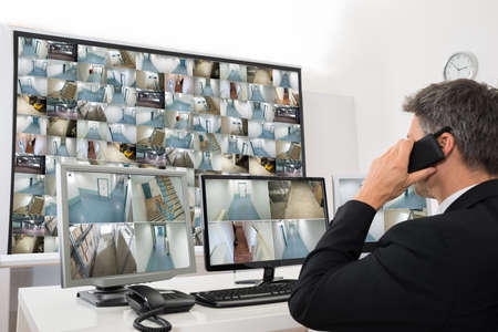 Foto für Security System Operator Looking At Cctv Footage While Talking On Telephone - Lizenzfreies Bild