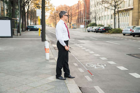 Photo pour Portrait Of A Blind Mature Man Crossing Road Holding Stick - image libre de droit