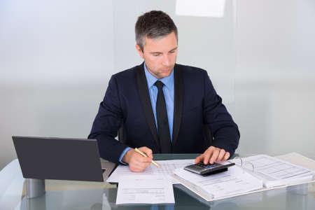 Photo pour Portrait Of A Businessman Calculating Finance In Office - image libre de droit