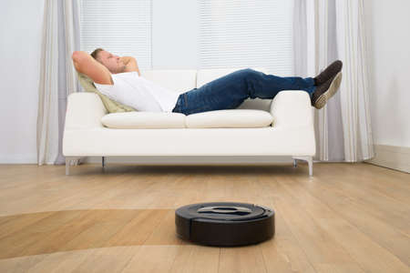 Foto de Man Relaxing On Sofa With Robotic Vacuum Cleaner On Hardwood Floor - Imagen libre de derechos