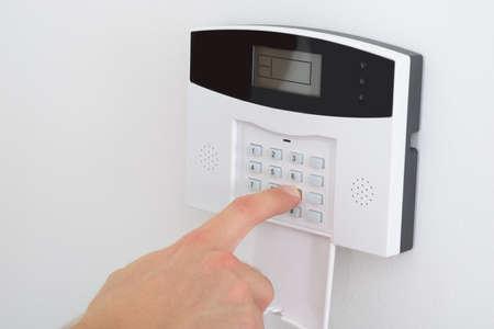Foto de Security Alarm Keypad With Person Arming The System - Imagen libre de derechos