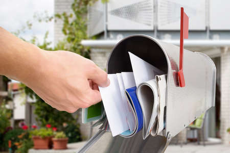 Photo pour Close-up Of Man's Hand Taking Letter From Mailbox Outside House - image libre de droit