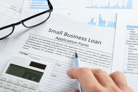 Photo for Hand With Pen And Calculator On Business Loan Application Form - Royalty Free Image