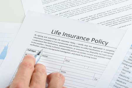 Photo pour Close-up Of Person Hand Filling Life Insurance Policy Application Form - image libre de droit