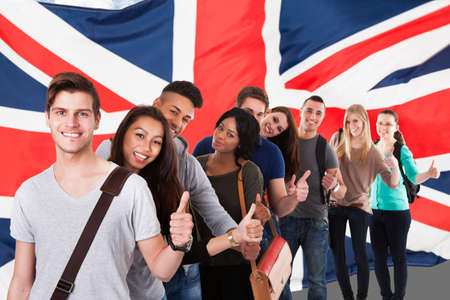 Photo pour Group Of Happy Multi Ethnic Students Standing In Front Of Uk Flag Showing Thumb Up - image libre de droit