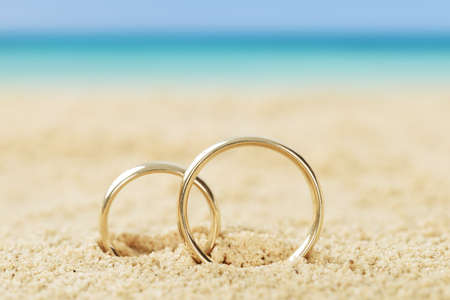 Photo pour Photos of wedding rings on sand at beach - image libre de droit
