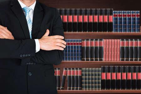 Foto de Close-up Of Male Lawyer With Arm Crossed Standing In Front Of Book Shelf - Imagen libre de derechos