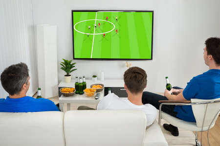 Photo for Three Men Sitting On Couch Watching Football Match On Television - Royalty Free Image