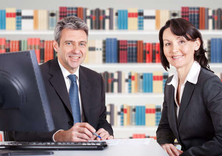 Photo for Two Happy Mature Businesspeople Sitting At Office Desk - Royalty Free Image