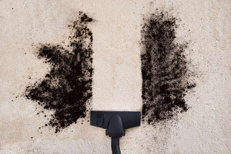 Photo pour High Angle View Of Vacuum Cleaner Cleaning Dirt On Carpet - image libre de droit