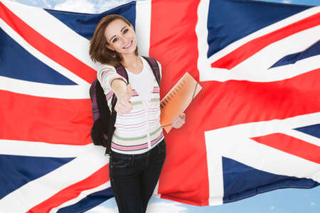 Foto de Young Female Student Gesturing Thumb Up In Front Of British Flag - Imagen libre de derechos