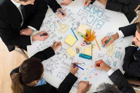 Foto de Group Of Businesspeople Discussing At Meeting In Office - Imagen libre de derechos