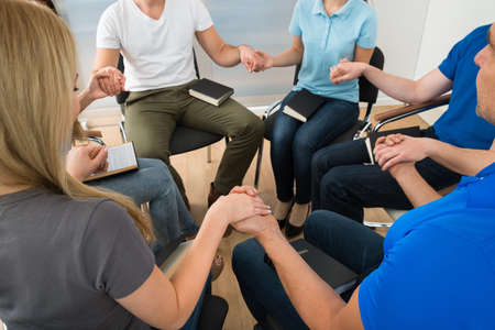 Photo for Close-up Of People Holding Each Others Hand Praying Together - Royalty Free Image