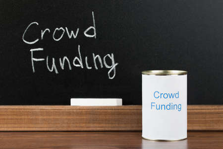 Crowd Funding Writing On Can In Front Of Blackboard And Chalk