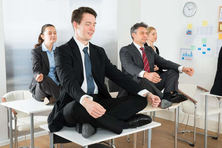 Photo for Meditating Businesspeople Sitting On Desk With Their Legs Crossed In Office - Royalty Free Image