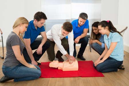 Foto de First Aid Instructor Showing Resuscitation Technique On Dummy - Imagen libre de derechos