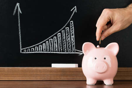 Foto de Hand Putting A Coin Into Piggy Bank In Front Of Blackboard Showing Graph - Imagen libre de derechos