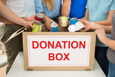 Photo pour Group Of People Putting Cans In Donation Box - image libre de droit