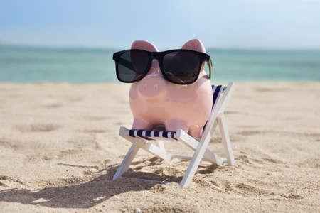 Foto de Piggy Bank On Deckchair With Sunglasses - Imagen libre de derechos