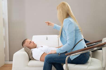 Foto de Female Psychiatrist Hypnotizing Patient Lying On Couch - Imagen libre de derechos