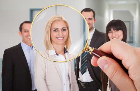 Photo pour Person Hand With Magnifying Glass Looking At Candidate - image libre de droit