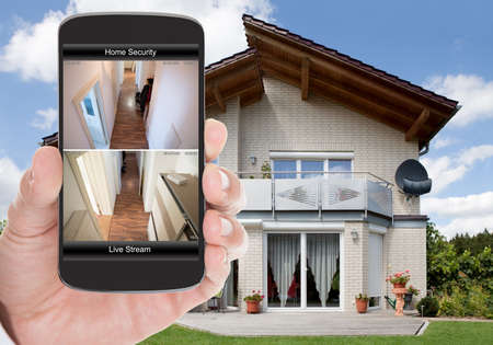 Foto de Close-up Of Person Hand Holding Mobile Phone With Home Security System - Imagen libre de derechos