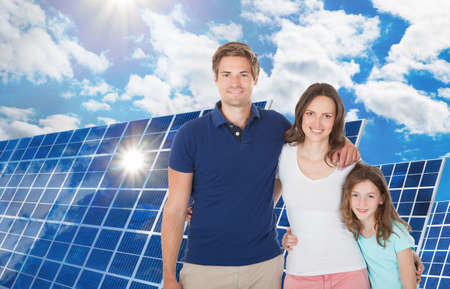 Photo pour Happy Family Standing Near The Large Solar Panel - image libre de droit