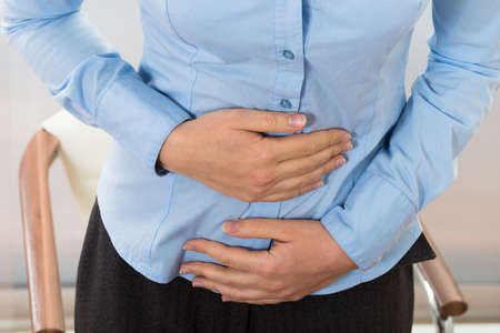 Photo for Close-up Of Businesswoman Suffering Stomachache In Office - Royalty Free Image