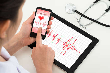 Photo pour Close-up Of Doctor Holding Mobile Phone With App For Health - image libre de droit