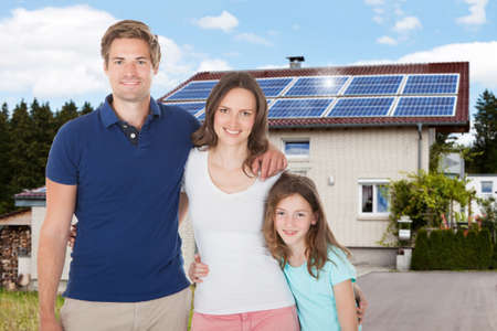 Photo pour Family Standing In Front House With Solar Panel On Roof - image libre de droit