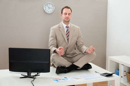 Photo pour Businessman Sitting On The Desk And Meditating With Eyes Closed - image libre de droit