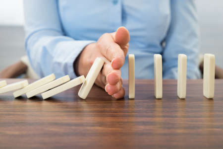 Foto de Close-up Of Businesswoman Stopping The Effect Of Domino With Hand At Desk - Imagen libre de derechos
