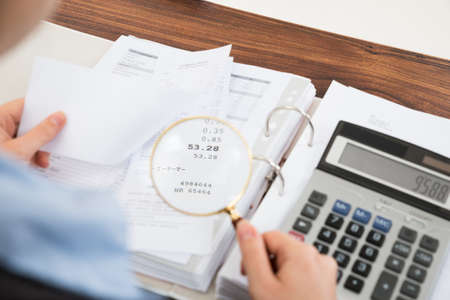 Photo pour Close-up Of Businessperson Examining Receipts With Magnifying Glass - image libre de droit