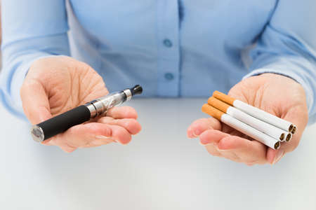 Foto de Close-up Of Businessperson Holding Electronic Cigarette In Hand - Imagen libre de derechos