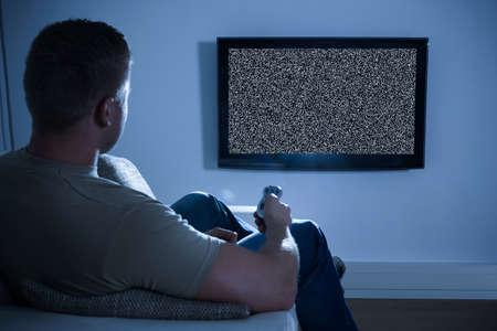 Foto de Man Sitting On Sofa In Front Of Television With No Signal - Imagen libre de derechos
