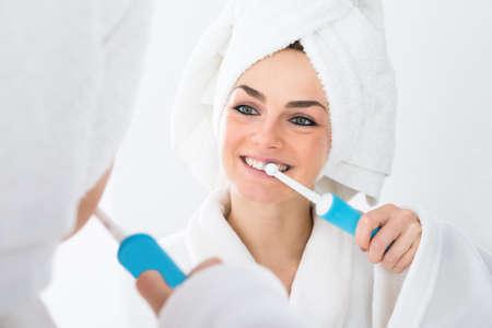 Photo pour Close-up Of A Woman In Bathrobe Brushing Teeth - image libre de droit