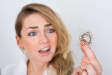 Foto de Close-up Of Worried Woman Holding Loss Hair - Imagen libre de derechos