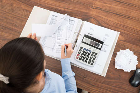 Photo pour Businesswoman Calculating Tax At Desk With Calculator In Office - image libre de droit
