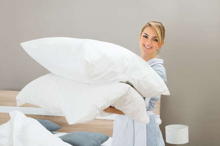 Photo pour Happy Female Housekeeping Worker With Pillows In Hotel Room - image libre de droit