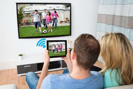 Foto de Couple Connecting Television And Digital Table Through Wifi Signal At Home - Imagen libre de derechos