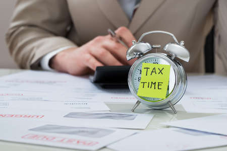 Photo pour Close-up Of Businessman With Tax Time Reminder Note On Alarm Clock At Desk - image libre de droit