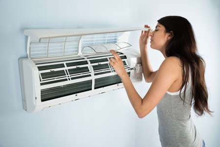 Photo for Young Woman Checking Air Conditioner In House - Royalty Free Image