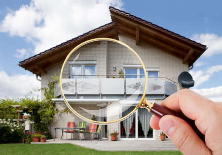 Photo for Person Hand With Magnifying Glass Over Luxury House - Royalty Free Image