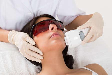 Photo pour Close-up Of Beautician Giving Epilation Laser Treatment On Woman's Face - image libre de droit